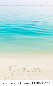 The Word Calm Written in the Sand on a Beach with morning sea background. Vertical composition