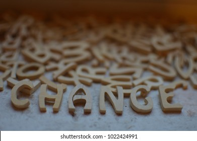 Word change written with wooden letters and other letters scattered in background