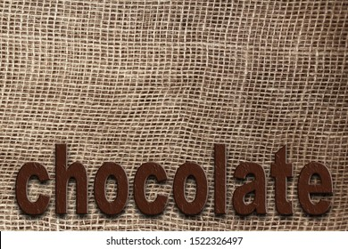 word chocolate on a background of natural canvas, burlap with a large weave, background and texture, close-up, copy space