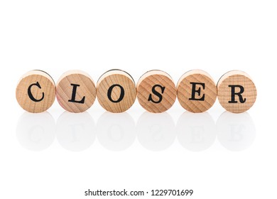 Word Closer from circular wooden tiles with letters children toy. Concept of nearness spelled in children toy letters.