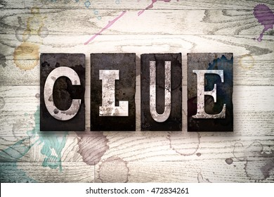 "The word ""CLUE"" written in vintage dirty metal letterpress type on a whitewashed wooden background with ink and paint stains."