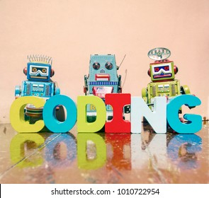 the word coding wit wooden letters on a old wooden floor with retro robot toys
