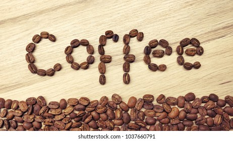 """The word """"Coffee"""" and fresh roasted coffee beans on a wooden background"""