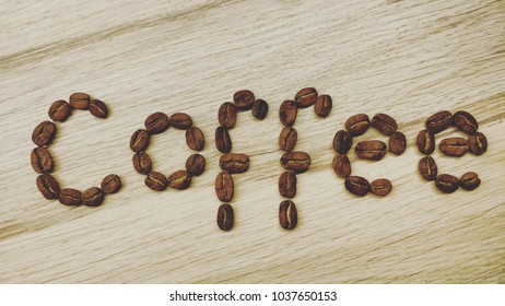 """Word """"Coffee"""" made or fresh roasted coffe beans on a wooden background"""