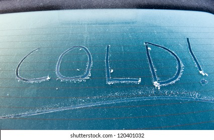 The word cold written on a frozen car screen