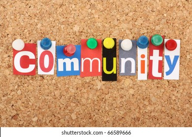 The word Community in cut out magazine letters pinned to a cork notice board with push pins