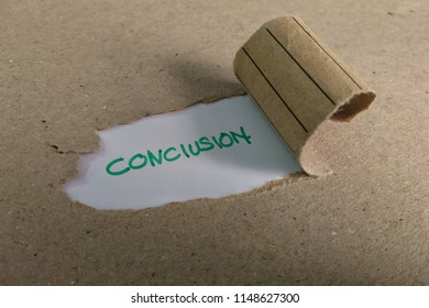 The word conclusion appearing behind torn brown paper.