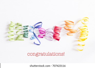 word congratulations on white background with paper streamer