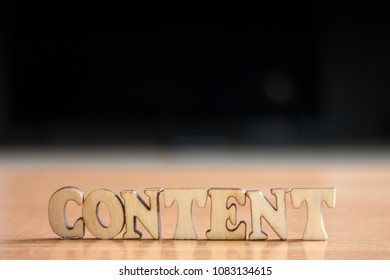 The word 'content' made of wooden letters. wood inscription on table and dark black background