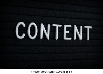 The word Content in white plastic letters on a black letter board