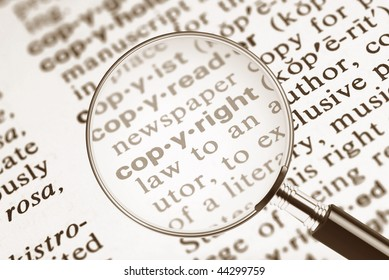 The word copyright from the dictionary under a magnifying glass. Shallow depth of field