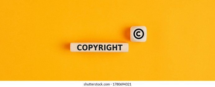 The word copyright and copyright symbol on wooden blocks on yellow background. Concept of patenting or copyright protection.