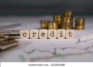 Word CREDIT composed of wooden letter. Stacks of coins in the background. Closeup