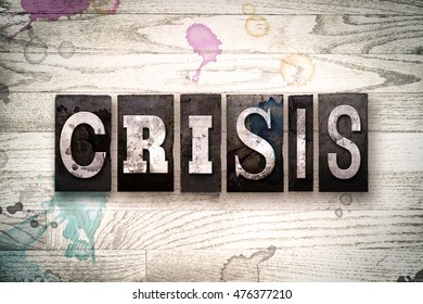 "The word ""CRISIS"" written in vintage, dirty metal letterpress type on a whitewashed wooden background with ink and paint stains."