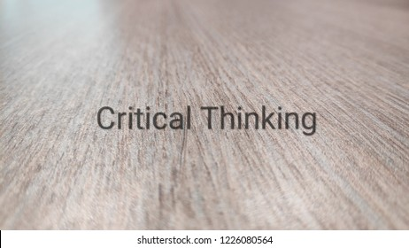 word critical thinking on wooden background.