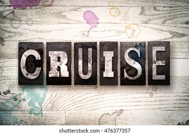 "The word ""CRUISE"" written in vintage, dirty metal letterpress type on a whitewashed wooden background with ink and paint stains."