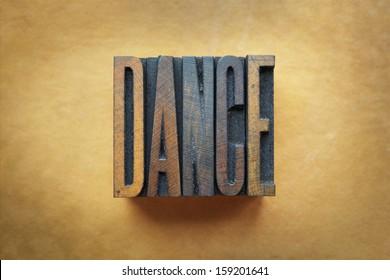 The word DANCE written in vintage letterpress type.