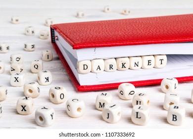 Word Darknet written in wooden blocks in red notebook on white wooden table. Wooden abc.