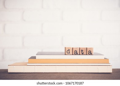 The word Data, alphabet on wooden cubes on top of books. Background copy space, vintage and minimal style. Research study or information analysis, facts and knowledge for education or business.