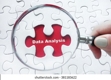 Word Data Analysis with hand holding magnifying glass over jigsaw puzzle