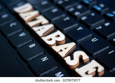 The word 'database' made of wooden letters. wood inscription on laptop keyboard background