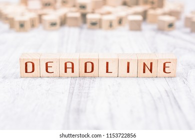 The Word Deadline Formed By Wooden Blocks On A White Table, Reminder Concept