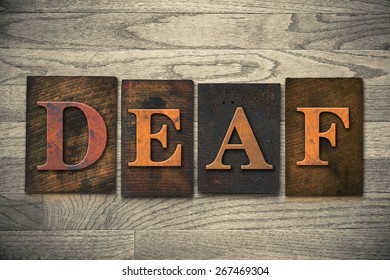 """The word """"DEAF"""" theme written in vintage, ink stained, wooden letterpress type on a wood grained background."""