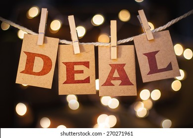 The word DEAL printed on clothespin clipped cards in front of defocused glowing lights.