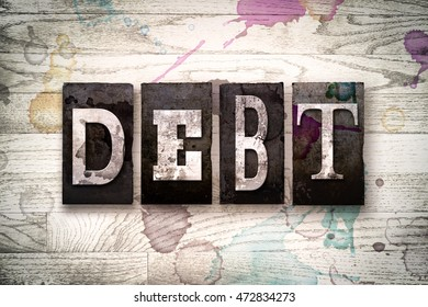"""The word """"DEBT"""" written in vintage dirty metal letterpress type on a whitewashed wooden background with ink and paint stains."""