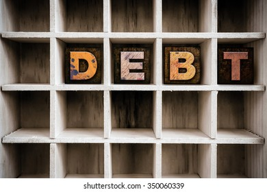 """The word """"DEBT"""" written in vintage ink stained wooden letterpress type in a partitioned printer's drawer."""