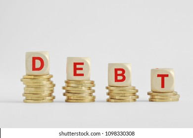 The word debt written with wood blocks on top of coins piles - Debt decrease concept