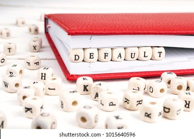 Word Default written in wooden blocks in red notebook on white wooden table. Wooden abc.
