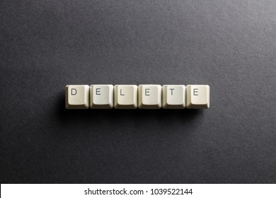 Word delete made using computer keyboard buttons on a black background. IT technology concept.