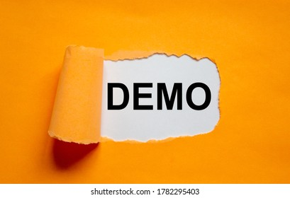 The word 'demo' appearing behind torn orange paper. Business concept. Copy space.