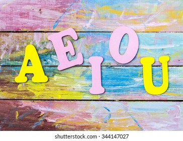 "Word design "" A E I O U "" show English Vowel by letterpress on painted wooden background"