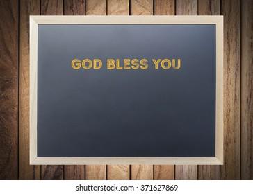 "Word design "" God bless you "" on black board over wooden  background"