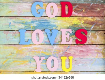 "Word design "" God Loves You"" by colorful letterpress   on  retro  painted wooden  background"