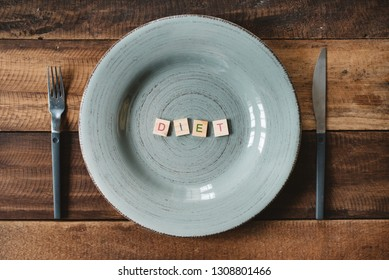 a word DIET made from a alphabet tiles in a empty plate. concept of dieting, lose weight and healthy eating