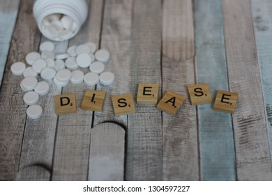 Word DISEASE written with Scrabble letters with spilled bottle of pills/tablets on vintage wooden table. Medical disorder and health problems. Editorial image, close up photo, studio shot.