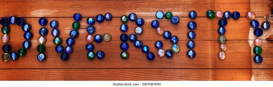 The word Diversity spelled out using marbles on a wooden board or plank to signify the importance of embracing variability, representation and individual differences. - Shutterstock ID 2007087890