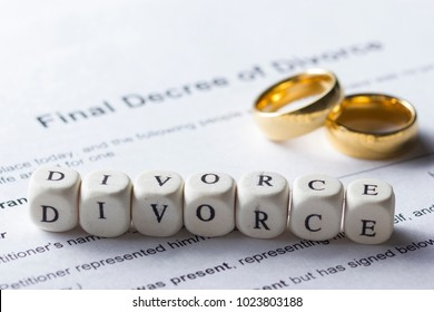 Word - Divorce made up of wooden letters on the table with wedding rings