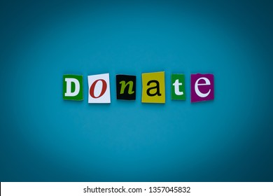 Word donate of cut letters on blue background. Donation concept. Headline - donate. A word writing text - donate. Banner with the inscription DONATE. Giving concept.