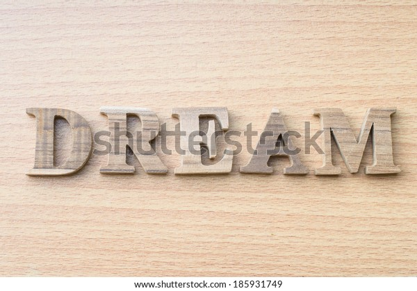 """the word """"DREAM"""" from wooden alphabet on wood background."""