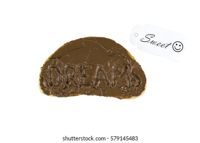 The word dreams carved in a chocolate covered loaf of bread. Sweet dreams concept.