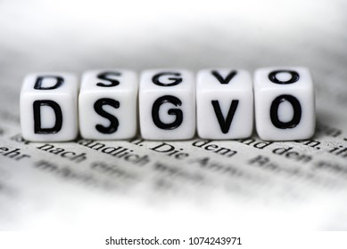 Word DSGVO formed by wood alphabet blocks on newspaper abbrevation for german law