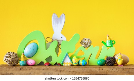 The word Easter in german language with easter bunny eggs and chicks