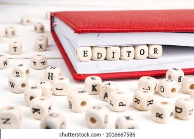 Word Editor written in wooden blocks in red notebook on white wooden table. Wooden abc.