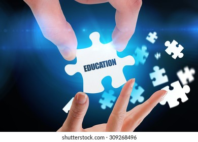 The word education and hands holding jigsaw against blue background with vignette