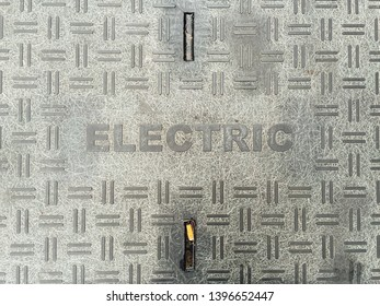 "Word ""electric"" marking a city street grate to electricy manhole"