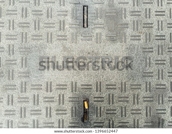 """Word """"electric"""" marking a city street grate to electricy manhole"""